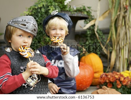 Brothers eating suckers they got trick or treating, focus on  knight with policeman blurred