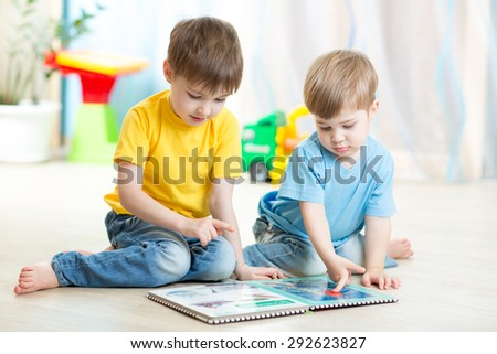 brothers kids read book together at home