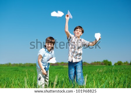 Brothers playing with paper planes in the green field
