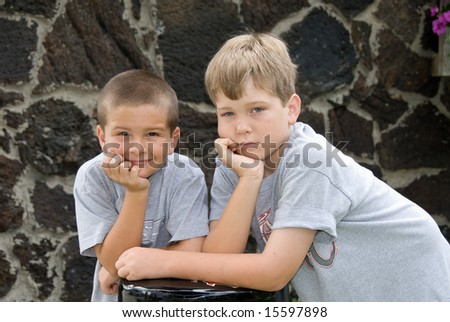 Brothers pose on a bar stool to show their boredom during a photo shoot.