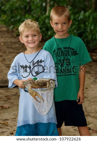 Brothers with their catch on a Caribbean beach - a larged clawed crab