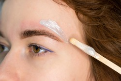 Brow master applying hot wax for brows epilation, lamination and waxing. Professional care for face and brow beauty procedures.