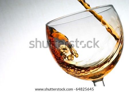 Brown alcohol liquid pouring into glass