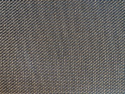 Brown and black speaker grill cloth from the vintage electric guitar amp cabinet. Background or texture.