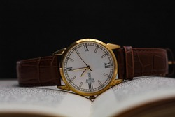 brown and gold wrist watch on book without trademark