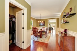 Brown and olive tones dining room interior. Large wooden table for six person. Open door to closet. Northwest, USA