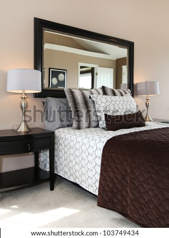 Brown and white bedroom close up with mirror and carpet.