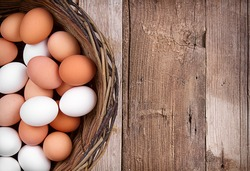Brown and white eggs in a wicker basket on a rustic wooden plank