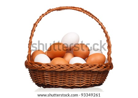 Brown and white eggs in the wicker basket over white background