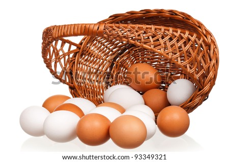 Brown and white eggs in the wicker basket over white background - stock photo