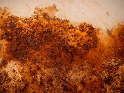 Brown and yellow rust on white enamel. Rusted brown and white abstract texture. Corroded white metal background. Rusted white painted metal wall. Rusty metal surface with streaks of rust.