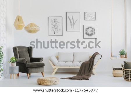 Brown armchair, wooden sofa and blanket in a bright living room interior. Real photo #1177545979