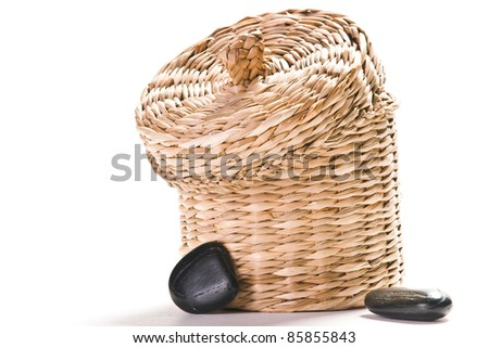 brown basket with black stones isolated on white ground