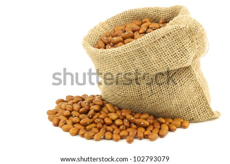 brown beans in a burlap bag on a white background