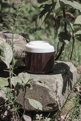 Brown beauty product container bottle with white cap for mock up standing on the wood in the nature under the sun. Idea for natural eco friendly cosmetics mock up