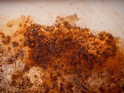 Brown, black and yellow rust and dirt on white enamel. Rusted brown and white abstract texture. Corroded white metal background. Rusty white painted metal wall.