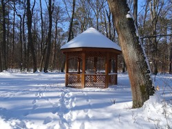 Brown bower covered by snow in park in Pokoj in Poland.