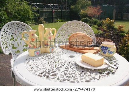 Brown Bread and Butter, on top of a bread board laid on a Garden Table, outside in a rear garden.  With oil & Vinegar jars during the summer on a sunny day