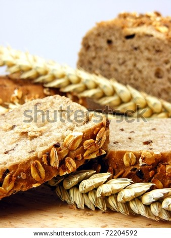 Brown bread & wheat on a wooden board