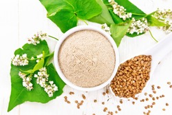 Brown buckwheat flour in a bowl, brown groats in a spoon, flowers and buckwheat leaves on white wooden board background from above