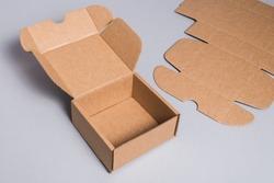Brown cardboard box on grey background, opened, empty inside