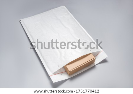 Brown cardboard box packed in white bubble envelopes on grey bac Foto d'archivio ©