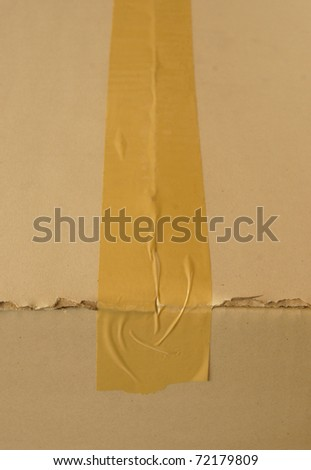 Brown cardboard box sealed with adhesive tape. - stock photo