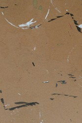 Brown cardboard texture of a drawing board for artists that has black and white paint and scratches and other misc markings.