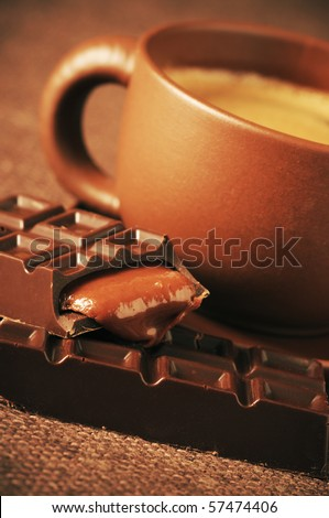 Brown ceramic cup of coffee and broken chocolate bar with caramel stuffing close-up on brown canvas. - stock photo