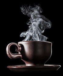 Brown ceramic cup of fresh steaming fragrant aromatic morning hot coffee over black background. Smoke from hot coffee.