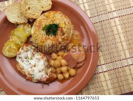 Brown ceramic dish on dish door: dish with Greek rice, parm steak, Maxixe, chickpeas with pepperoni sausage and bacon, toast to accompany. Brazil #1164797653
