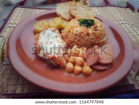 Brown ceramic dish on dish door: dish with Greek rice, parm steak, Maxixe, chickpeas with pepperoni sausage and bacon, toast to accompany. Brazil #1164797848
