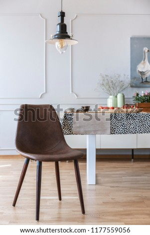 Brown chair under lamp in white dining room interior with table and wall with molding. Real photo