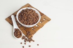 Brown Chana in a bowl isolated on white background with spoon and table mat