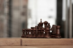 brown chess board with figures on a wooden table in a cafe, playing chess