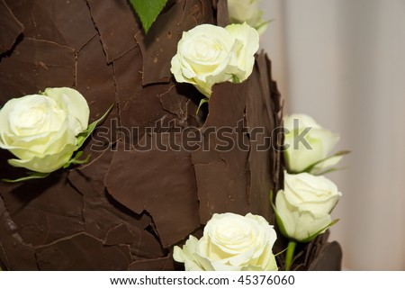 Brown chocolate wedding cake decorated with light yellow roses