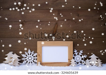 Brown Christmas Card With White Christmas Decoration On Snow. Picture Frame With Copy Space For Advertisement. Snowflakes, Christmas Trees. Rustic Wooden Background. Snowing And Snowy Atmosphere