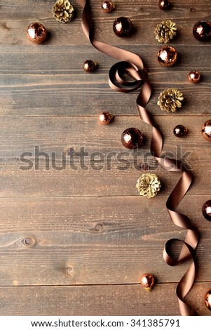 Brown Christmas ornaments with ribbon on wooden background #341385791