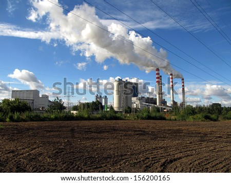 brown-coal power plant with chimney giving off large amounts of gas to the blue sky