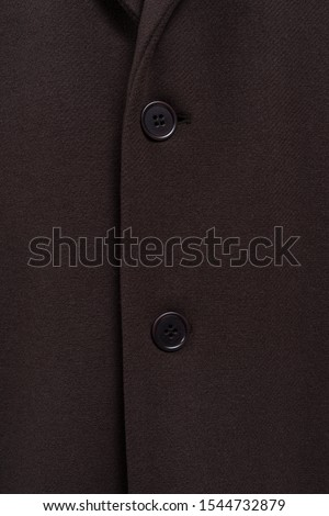 Brown coat texture closeup. Two buttons on woolen clothes. Classic outfit sample.  Buttoned up. #1544732879