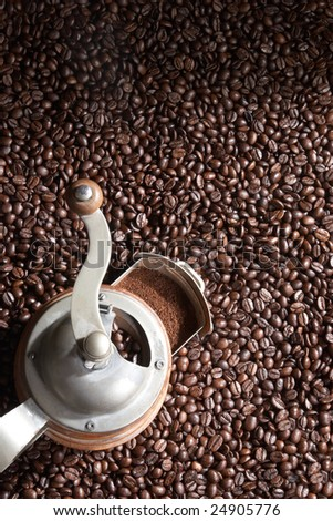 Brown coffee beans with coffee grinder covers the whole picture