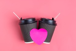 Brown coffee cups, purple heart-shaped sticker on pink background. love is. Concept for coffee lovers, love is. Happy Valentine's Day Flat lay Top view Mock up Copy space Place for text
