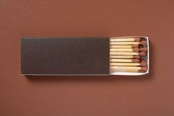 brown color matchbox and brown match sticks on a brown background