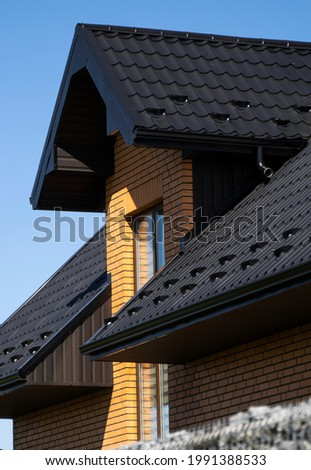 Brown corrugated metal profile roof installed on a modern house with a attic windows. The roof of corrugated sheet. Roofing of metal profile wavy shape. Modern roof made of metal. Metal roofing.