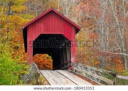 Brown County Indiana's Bean Blossom Covered Bridge, built in 1880 and seen here surrounded by colorful fall foliage, is a very rare example of a Howe single truss structure.