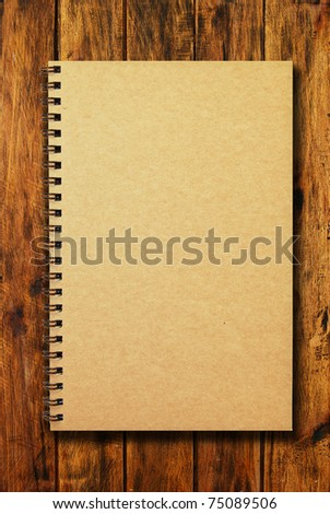 brown cover notebook on natural wood texture background