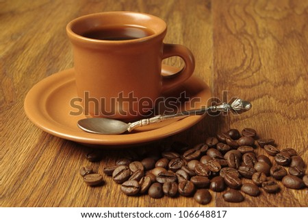 Brown cup of coffee with beans over wooden background