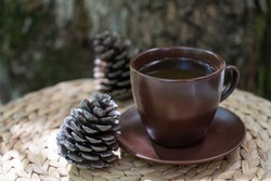 Brown cup of herbal tea, two cones on straw table on textured wood background. Healthy lifestyle, organic beverages for healthy living, alternative medicine.