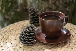 Brown cup of herbal tea, two pine cones  on straw table on natural background.. Healthy lifestyle, organic beverages, alternative medicine.