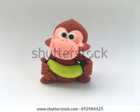 Brown cute and lovely cartoon clay monkey smile is lifting yellow banana on hand in white background in concept enjoy ,happy,naughty ,healthy ,exercise